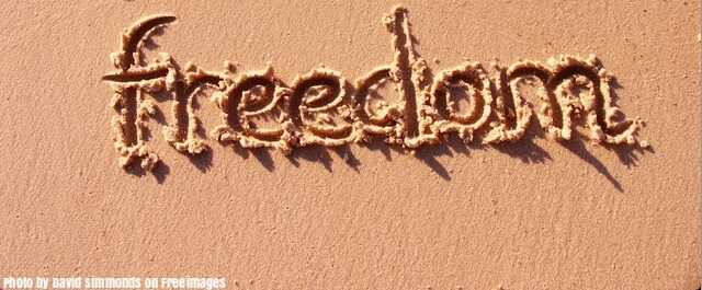 """The word """"freedom"""" written on the sand."""