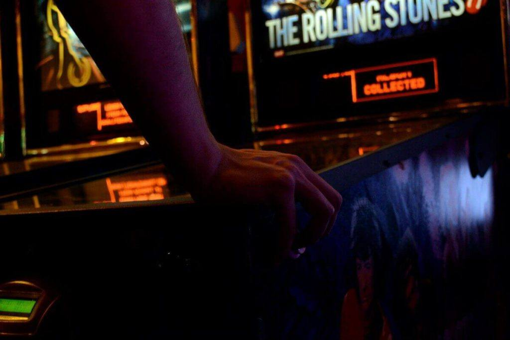 Someone playing a Rolling Stones pinball machine