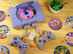 The original PlayStation with two controllers and a bunch of games